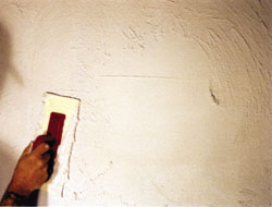 A plaster overcoat renews the wall's stucco-like appearance. Once dry, brush away any loose plaster, then prime and paint the surface.