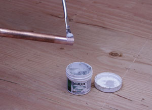 Apply flux to copper pipe and the interior of fittings with a small brush.