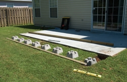 If your new deck will extend beyond the existing patio, lay out the pier blocks as needed.