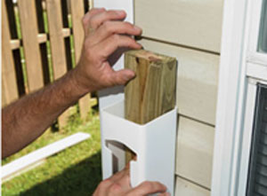 Inserting a pressure-treated 2x4 gives the vinyl newel post strength when anchored to the house framing.