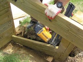 For the sides, I ran a kicker between posts rather than excavating the entire hill. The kicker, wihich rests underground on the exterior side of the decking acts as a nailing surface for the return walls.