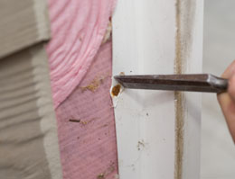 Using a chisel to cut the vinyl flange around nail heads can be a good way to release the flange.