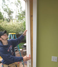 With the interior and exterior trim removed and the flanges free of nails, pull the frame out at the top.