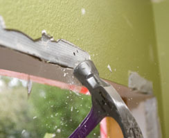This patio door had a drywall surround. Hitting the metal corner bead with a hammer removes joint compound and raises the edges of the metal for removal.