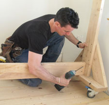 With the top of the upright held securely, predrill and toe-screw a 2x6 stretcher to the center of the upright assembly.