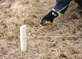 Pull the line tightly between corner stakes, then stake the line intermittently.