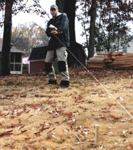"With the line in place, measure for the fence post locations and spray paint an ""X"" over the exact spot to dig."