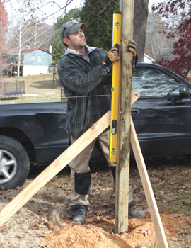 A traditional method to plumb and brace posts is to use a 4-foot level and a couple of pivoting wood legs.