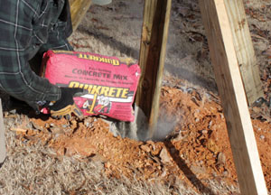 Quikrete Fast-Setting Concrete can be poured easily into the post hole dry. No mixing is required.