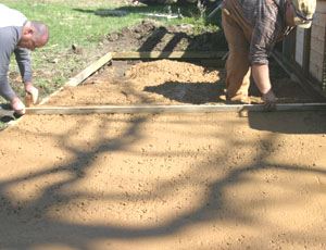 A screed board is used to level the concrete to the form boards.