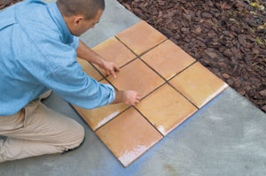 Place and align the tiles How to Lay Tile over a Concrete Patio