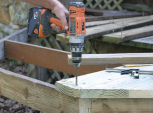 The deck boards are notched to fit around posts. Mark the cutouts and bore starting holes with a 3/4-inch spade bit.