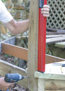 Plumb and square the posts, fastening to the joists with pairs of 1/2-inch diameter through-bolts and washers.