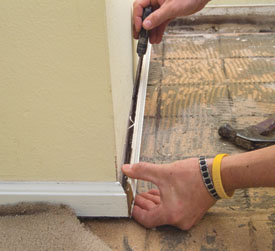 A stiff blade putty knife is a good tool for getting behind baseboards for removal.