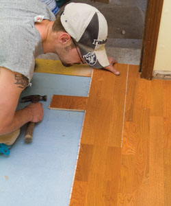 Use scrap flooring material as the beater block between your hammer and the flooring when snapping pieces into position.