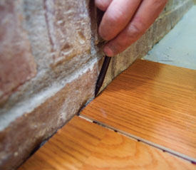 When marking the layout lines to cut an angle at the floor transition, be sure to put the flooring pieces in position as much as possible by placing the bottom edge of the groove on top of the tongue so the piece is marked in the same position as when the pieces are snapped together.