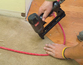 We trimmed the existing carpet to match the flooring transition and tacked the carpet into place wit ¼-inch crown staples.