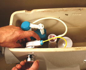Clip the fill line to the overflow tube of the flush valves, and then screw the flush handle in place.