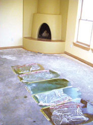 Stain samples are shown in a bedroom which is slated to receive carpet. The plastic is a texturing device used with some colors.