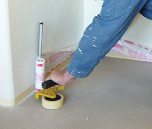 Over a layer of medium-tack masking tape close to the floor, a masking machine applies tape and thin plastic, which is then unfolded up the wall to a height of 2 feet and tacked into place.