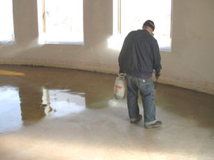 A worker sprays a heavy coat of stain on a cleaned and dry floor. This living room reacted strongly and required only one application of stain.