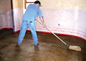 A worker uses a micro fiber mop for final rinsing during the post-stain scrub.