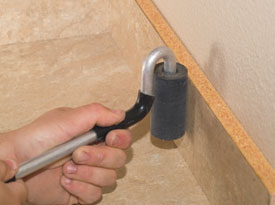 We use a small roller to press the laminate onto the backsplash.