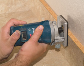 Trim the laminate flush with the top of the backsplash boards with a laminate trim router