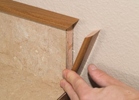We machine and fasten a small wood cap that slightly overhangs the laminate back splash.