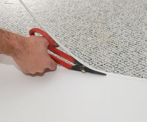 After scribing the material with a pencil, we use tin snips to trim the laminate to fit.