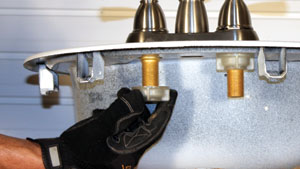 7. Insert the threaded shanks of the faucet through the holes of the sink and secure them from below with new wing nuts.