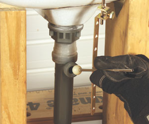 """19. Install the ball-and-socket lift lever in the drain. Thread the short end of the lift lever (near the ball) through the hook in the new drain cap. The """"ball"""" is secured in the drain pipe with a nut."""