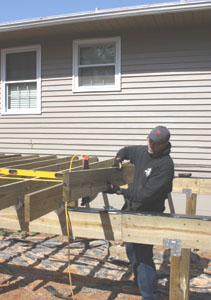 Deck joists are often supported by beams built from two large pieces of lumber, 2×8 or larger. The deck joists can be connected to the beam with metal hurricane brackets.