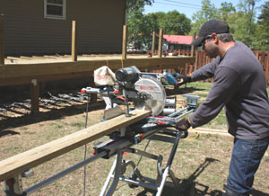 Tool setups are key to an organized project. Here we use a Bosch sliding miter saw with an out feed support stand to cut the deck boards to length (www.boschtools.com).