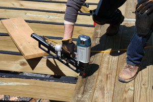 A pneumatic framing nailer with ring-shank nails can make quick work of installing a pressure-treated deck.