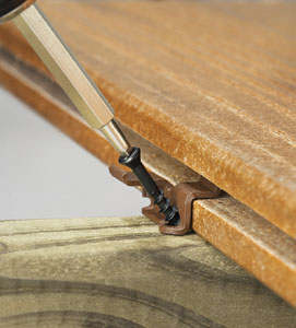 Some composite decking manufacturers offer fastener systems that are hidden inside the grooved edges between the deck boards. Show here is a ConceaLoc hidden fastener from Timbertech.