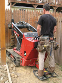 I used the Toro Dingo with auger attachment for this fence and it worked great for drilling holes--even in zero clearance applications.