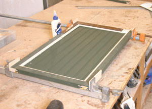 The beadboard panels are cut and their back edges routed or sawn to create a 1/4- inch thickness, then the doors glued together and clamped.