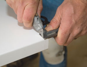 Use your utility knife and combo square to score the door across the face.