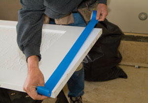 Protect the door surface with masking tape. This helps prevent the saw base from leaving marks on the door.