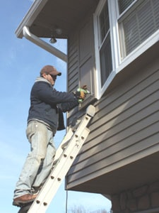 The urethane shutters are light enough for one man to install. Just zip in a couple of screws at the top to support the weight, and that's enough to hold the shutter in place while you finish the installation.