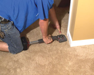 Use a knee-kicker to push the carpet over the tack strips.
