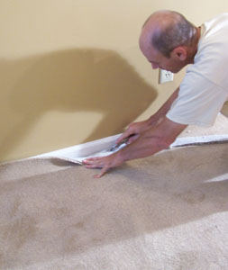 Proceed down the wall between the installed corners, anchoring the carpet and trimming the excess.