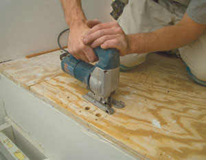 Determine the location of the floor opening for the newel post tenon. Drill the corners with a spade bit and cut out the floor boards with a jigsaw.