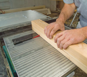 A table saw outfitted with a sliding bevel guide was used to cut a kerf all the way around the newel post at the elevation where the trim board meets the newel post.