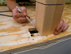 Position the newel post over the hole to mark the size of the tenon on the bottom of the post.
