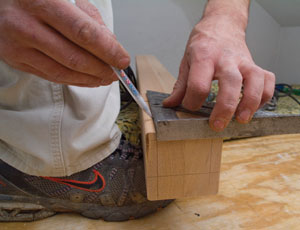 Extend the layout lines for the newel tenon across the bottom of the post and up to the shoulder cut.