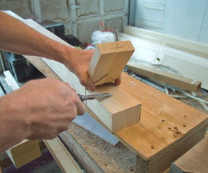 Use a wood chisel to snap the slabs off the side of the tenons and to finish cleaning up the cuts.