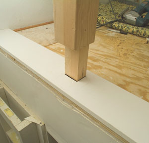 Note that the newel post tenon extends through the trim board and into the floor.
