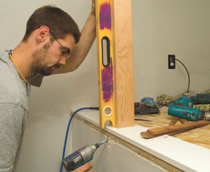 When anchoring the newel post through the rim joist and into the newel tenon, keep checking the post for plumb in both directions.